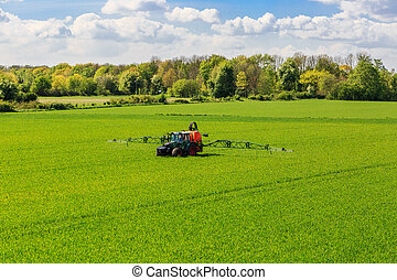 tractor spraying glyphosate pesticides on a field - tractor...