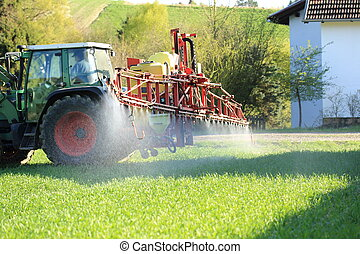 Tractor spraying pesticide near houses