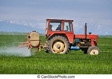 Tractor spraying pesticides on a wheat field