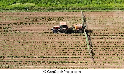 Tractor spraying pesticides on vegetable field with sprayer...