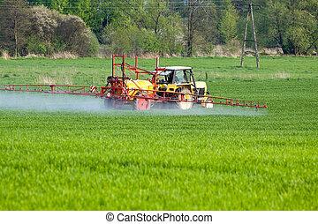 Tractor spraying a field on farm