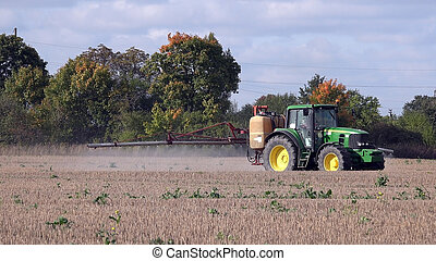 Tractor spraying stubble field with herbicide chemicals in...
