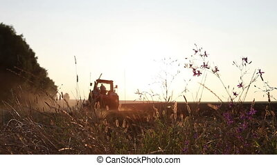 tractor stands in a field of black earth at sunset