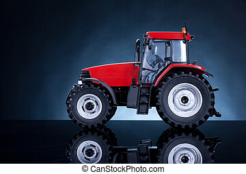 Tractor studio shot on blue background. Side view.