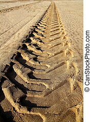 tractor tires pneus footprint printed on beach sand desert
