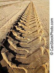 tractor tires pneus footprint printed on beach sand desert