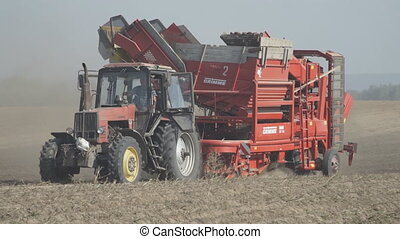 Tractor trailed harvester rides on a dusty field and...