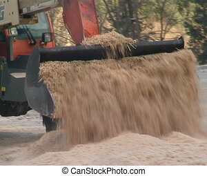 Tractor transporting sawdust sifting to boiler house.