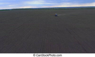 Tractor treats the field, shooting from the air