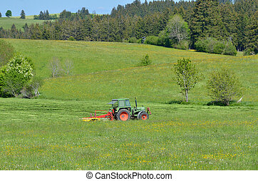 tractor while cutting - tractor on meadow in alps, Germany...