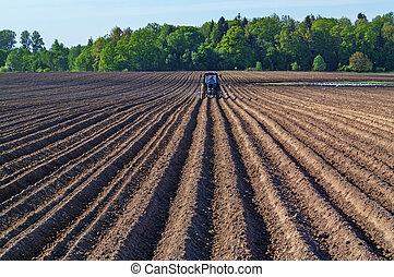 Tractor with a seed drill on a plowed field.