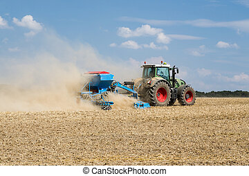 Tractor with a sowing machine working in the field