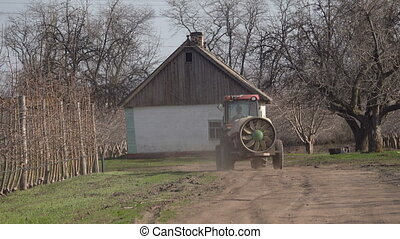 Tractor with a sprayer in the garden in early spring