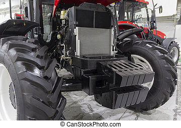 Tractor with an open hood in the exhibition hall. Industry