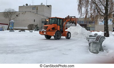 Tractor with bucket cleans or removes snow in one heap. Snow removal in the city square.