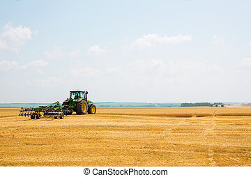 Tractor with cultivator in a field
