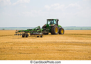 Tractor with cultivator in a field - Tractor linked up with ...