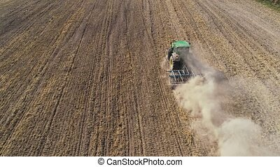 Tractor with disc harrows on the farmland - aerial footage...