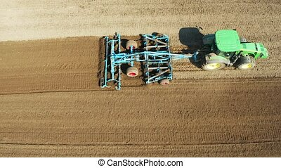 Tractor with disc harrows on the farmland - aerial view farm...