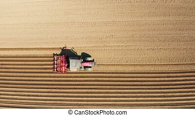Tractor with disc harrows on the farmland - aerial view...