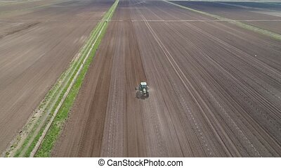 Tractor with harrows on the farmland - Aerial view of...