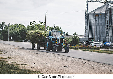 Tractor with hay wagon. Tractor pulling a trailer with hay across a bridge