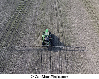Tractor with hinged system of spraying pesticides. Fertilizing with a tractor, in the form of an aerosol, on the field of winter wheat.