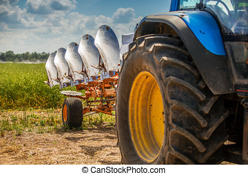 tractor with plough beside the field