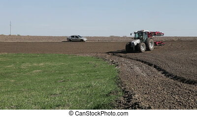 tractor with plow move with plowed field on untilled spring