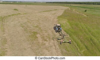 Tractor with rake tedders on the farm field. - Aerial, view...
