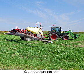 tractor with sprayer on field