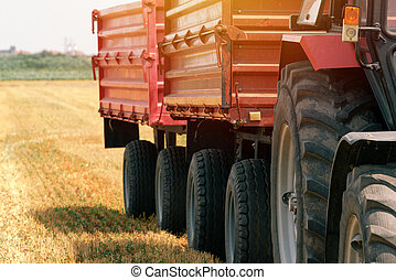 Tractor with wagon trailer in field