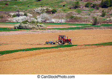 tractor working in a field at spring