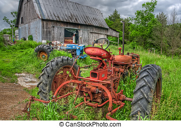 Tractors in Weeds - Two old rusty tractors sit abandoned in...