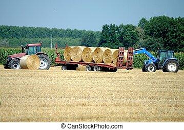 tractors load bales of hay in farmlands