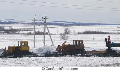 Tractors transport drilling equipment through mud