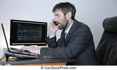 trader advises client on a phone and watching currency...