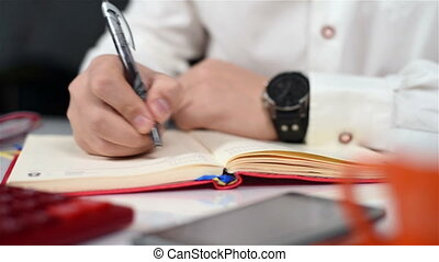 Trader Man Working In Office And Taking Notes In Diary. Close Up