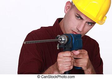 Tradesman aiming a power tool