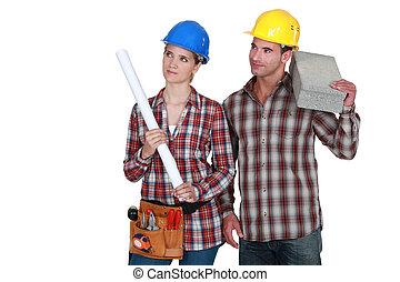 Tradesman and tradeswoman looking sideways