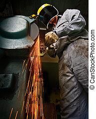 Tradesman at work grinding steel.