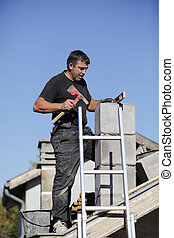 Tradesman building a chimney stack