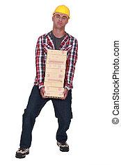 Tradesman carrying a heavy load of bricks