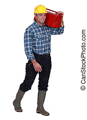 Tradesman carrying his toolbox on his shoulder