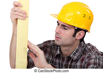 Tradesman checking the quality of his wood