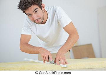 Tradesman cutting insulation