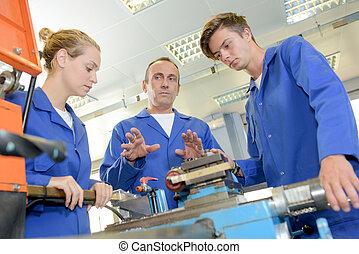Tradesman explaining exquipment to trainees