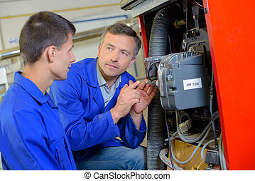 Tradesman explaining machinery to apprentice