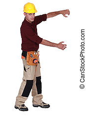 Tradesman framing an invisible object with his arms