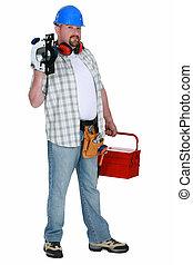 Tradesman holding a circular saw and his toolbox